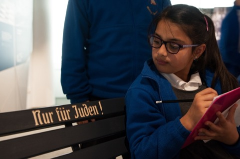 A school child sits on the replica bench marked 'Nur fur Juden' (Only for Jews) in the Holocaust Exhibition and Learning Centre.