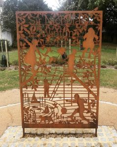 Metal memorial showing Nicholas Wintons name, with children playing games