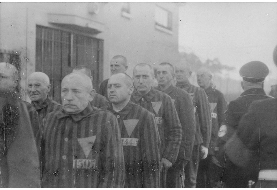 Black and white photo of men wearing striped prison uniforms with downward-facing triangles and numbers